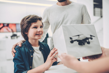 Cropped image of handsome young man and his cute son are in modern light quadcopter store. Buying the appropriate drone