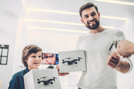 Handsome young man and his cute son are in modern light quadcopter store. Choosing the appropriate drone Archivio Fotografico - 96719079