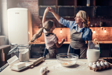 Grandmother and granddaughter are cooking on kitchen. Making tasty baking together. Dancing and having fun together. Imagens