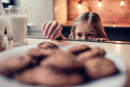Little cute girl on kitchen is taking chocolate cookie from table.