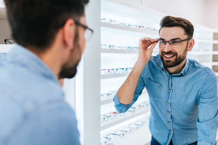 Handsome young man is choosing the most appropriate eyeglasses in modern ophthalmology clinic.