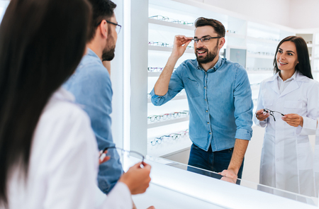 Young female doctor ophthalmologist is helping handsome man to choose the most appropriate eyeglasses. Doctor and patient in modern ophthalmology clinic Banco de Imagens - 97150463
