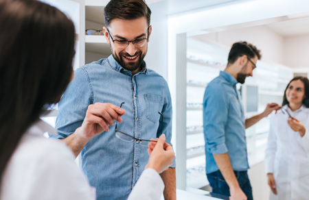 Young female doctor ophthalmologist is helping handsome man to choose the most appropriate eyeglasses. Doctor and patient in modern ophthalmology clinic