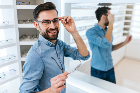 Handsome young man is choosing the most appropriate eyeglasses in modern ophthalmology clinic. Banco de Imagens - 97151860