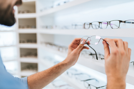 Cropped image of handsome young man is choosing the most appropriate eyeglasses in modern ophthalmology clinic.