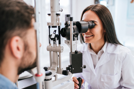 Attractive female doctor  ophthalmologist is checking the eye vision of handsome young man in modern clinic. Doctor and patient in ophthalmology clinic.