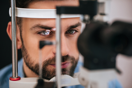 Handsome young man is checking the eye vision in modern ophthalmology clinic. Patient in ophthalmology clinic Stock Photo