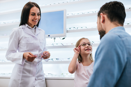 Handsome young man and his little cute daughter are choosing the best apropriate eyeglasses in modern ophthalmology clinic. Dad and daughter with doctor ophthalmologist. Foto de archivo - 98053508