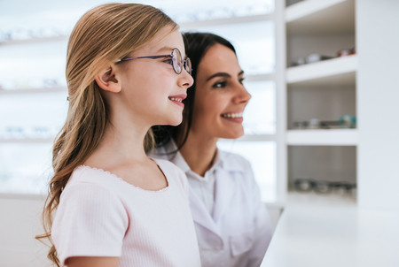 Attractive female doctor ophthalmologist is helping little cute girl to choose the best eyeglasses in modern ophthalmology clinic. Banque d'images