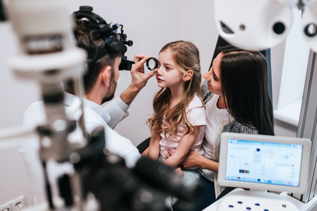Handsome male doctor  ophthalmologist is checking the eye vision of little cute girl in modern clinic. Mom with daughter in ophthalmology clinic.