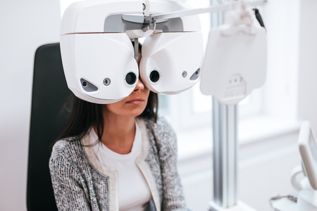 Attractive young woman is checking the eye vision in modern clinic. Patient in ophthalmology clinic Stock Photo