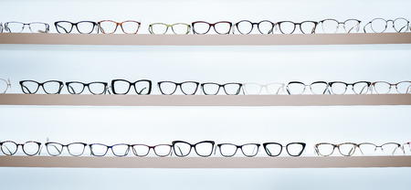 Big choice of eyeglasses on shelves in ophthalmology clinic. Modern light ophthalmology clinic. Stock Photo