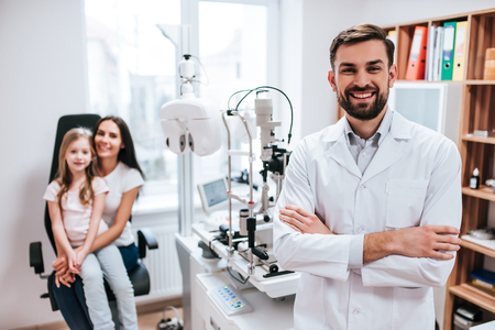 Handsome male doctor  ophthalmologist is checking the eye vision of little cute girl in modern clinic. Mom with daughter in ophthalmology clinic. Zdjęcie Seryjne - 97162225