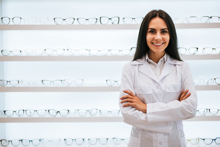 Attractive young female doctor in ophthalmology clinic. Doctor ophthalmologist is standing near shelves with different eyeglasses. Stock Photo