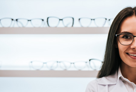 Cropped image of attractive young female doctor in ophthalmology clinic. Doctor ophthalmologist is standing near shelves with different eyeglasses. Foto de archivo - 97162226