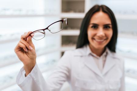 안과 클리닉에서 매력적인 젊은 여성 의사. 안과 의사는 다른 안경이 달린 선반 근처에 서 있습니다.