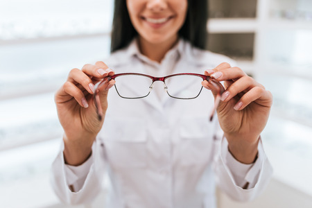 Cropped image of attractive young female doctor in ophthalmology clinic. Doctor ophthalmologist is standing near shelves with different eyeglasses.