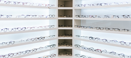 Big choice of eyeglasses on shelves in ophthalmology clinic. Modern light ophthalmology clinic.