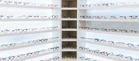 Gran variedad de anteojos en estantes en clínica oftalmológica. Clínica moderna de oftalmología ligera.