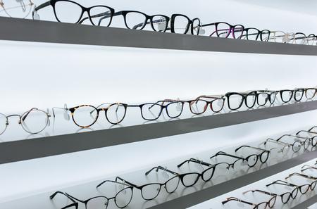Big choice of eyeglasses on shelves in ophthalmology clinic. Modern light ophthalmology clinic.