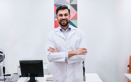 Young handsome male doctor ophthalmologist is working in modern ophthalmology clinic.