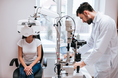 Handsome male doctor  ophthalmologist is checking the eye vision of attractive young woman in modern clinic. Doctor and patient in ophthalmology clinic. 版權商用圖片