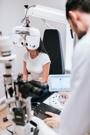 Handsome male doctor  ophthalmologist is checking the eye vision of attractive young woman in modern clinic. Doctor and patient in ophthalmology clinic. Stockfoto