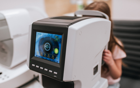 Little cute girl is checking the eye vision in ophthalmology clinic. Tools for checking the eye vision and eye health in modern ophthalmology clinic.