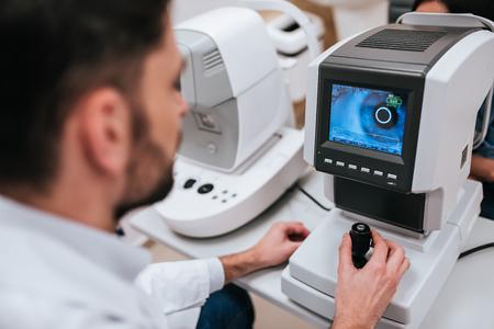 apuesto oftalmólogo médico masculino está examinando la vista del ojo de la mujer joven atractiva en uniforme atractivo del negocio y paciente en clínica ultrasónica Foto de archivo