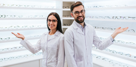 Doctors in ophthalmology clinic. Two ophthalmologists are standing near shelves with big choice of different eye glasses.