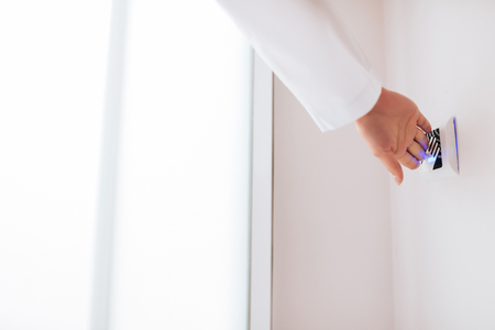 Modern technologies. Cropped image of female doctor is opening the door using sensor button in modern light clinic.