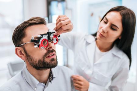 atractiva oftalmólogo femenino está examinando la vista del estudio del hombre joven guapo en uniforme moderno clínica y paciente en clínica ultrasónica