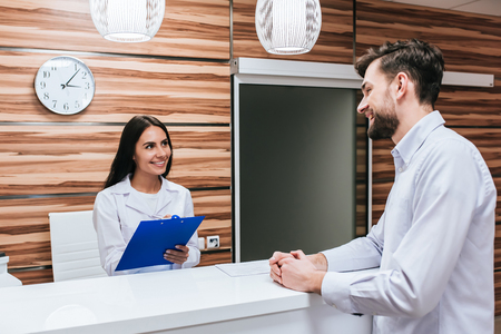 Young female doctor  and handsome patient are standing on reseption desk in modern clinic