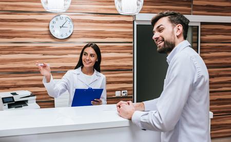 Jonge vrouwelijke arts en knappe patiënt staan op reseption desk in moderne kliniek