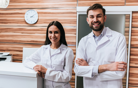 Two doctors are standing near reception desk in modern clinic.