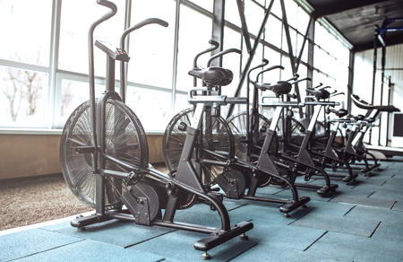 Modern empty light gym. Row of exercise bikes. Cycling