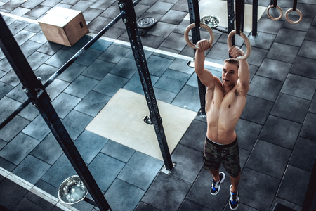 Strong muscular man is working out in gym. Cross fit training. Shirtless man on athletics rings.