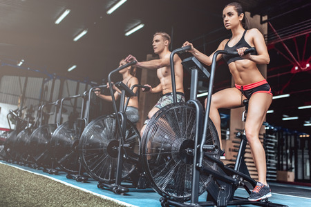 Group of sporty muscular people are working out in gym. Cross fit training. Two attractive women and handsome man are doing cycling on exercise bikes.