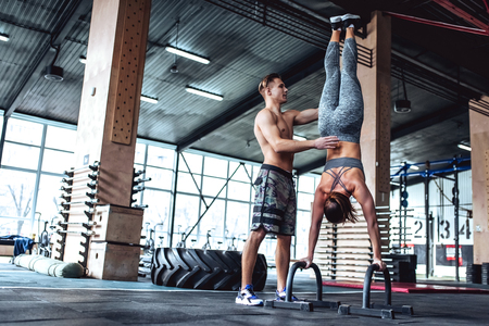 Handsome muscular man and attractive sorty woman are working out in gym. Couple making cross fit training.