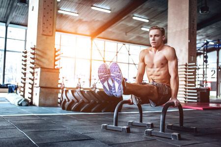 Strong muscular man is working out in gym. Cross fit training. Stock Photo