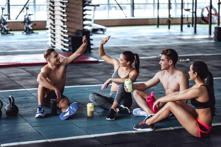 Group of sporty muscular people are working out in gym. Cross fit training. Having rest together Imagens