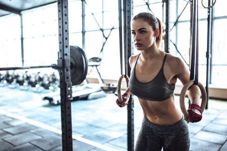 Attractive young sporty woman is working out in gym. Cross fit training. Muscular woman with athletics rings