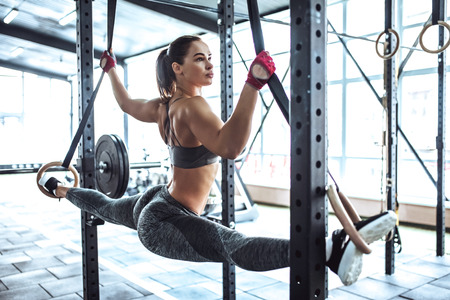 Attractive young sporty woman is working out in gym. Cross fit training. Muscular woman with athletics rings. Stretching and doing splits.