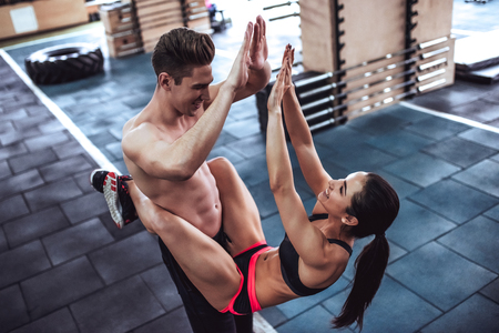 Handsome muscular man and attractive sporty woman are working out in gym. Couple making cross fit training. Abs exercise. Imagens