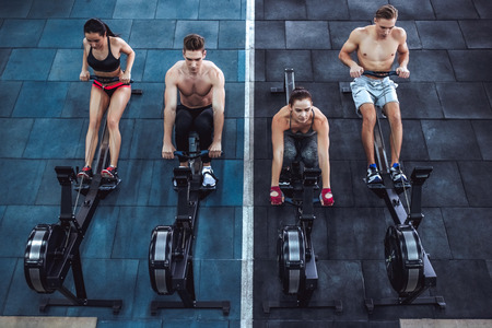 Group of sporty muscular people are working out in gym. Cross fit training. Paddling training apparatus. Top view of four sportsmen are rowing together.