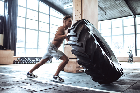 Strong muscular man is working out in gym. Cross fit training. Pushing tire. Imagens