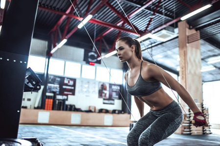 Attractive young sporty woman is working out in gym. Cross fit training. Upper body exercise.
