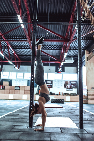 Attractive young sporty woman is working out in gym. Cross fit training. Doing the headstands.