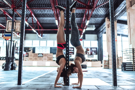 Two attractive sporty women are working out in gym. Cross fit training. Doing the headstands.