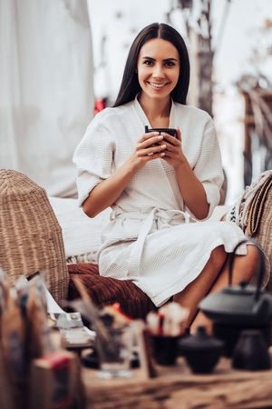 Attractive young woman is relaxing in spa and wellness center and drinking tea. Beauty treatment concept.